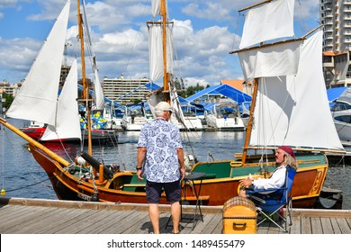 Coeur d'Alene, Idaho - August 25 2019: A visitor to the Coeur d'Alene Wooden Boat show talks with a boat owner dressed as a pirate about his miniature replica ship docked at the marina