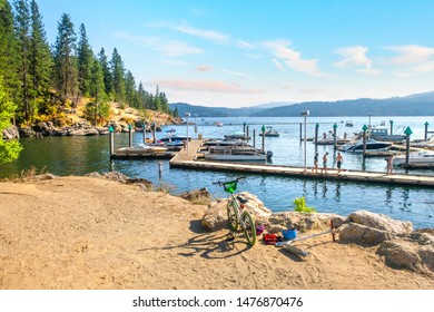 Coeur d'Alene, Idaho - August 4 2019: A child's scooter and bicycle sit on the shores of Lake Coeur d'Alene near the resort marina as a group of teens walk along the boardwalk past docked boats.