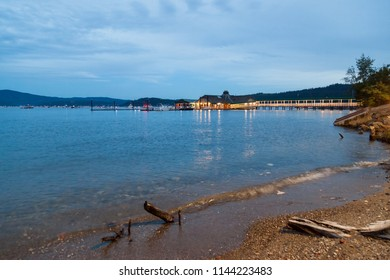 COEUR D'ALENE, IDAHO / USA - JULY 4, 2018: The Cedars floating restaurant on Lake Coeur d'Alene at twilight with boats in the background on the Fourth of July in Coeur d'Alene, Idaho.