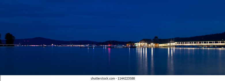 COEUR D'ALENE, IDAHO, USA - JULY 4, 2018: The Cedars floating restaurant on Lake Coeur d'Alene at twilight with boats in the background on the Fourth of July in Coeur d'Alene, Idaho.
