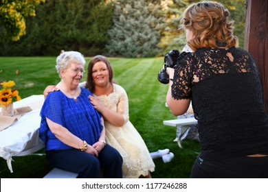COEUR d'ALENE, IDAHO, USA - September 1, 2018: A wedding photographer prepares her camera during a photo shoot with a bride and her grandmother