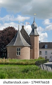 Coevorden, The Netherlands, July 28, 2020: the medieval castle surrounded by a garden with tall grass and a red beech tree under a cloudy sky