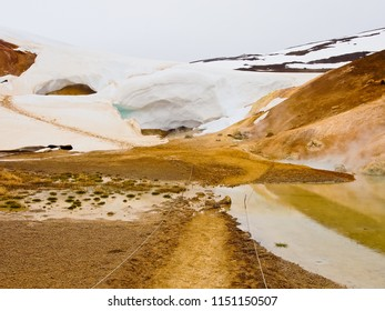 coexistence of hot spring pool and cold snow next stora-viti crater in krafla volcanic zone myvatn lake iceland