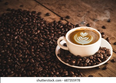 Cofee cup Espresso and Coffee beans with Hot latte art on wooden background. side view with copy space for your text