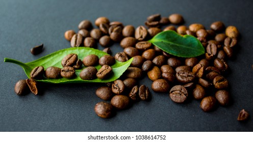 coffe beans and green leaf on black background