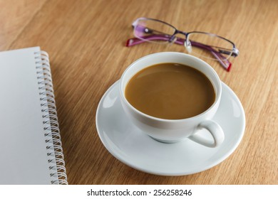 Coffe cup, note book and glasses on wooden table