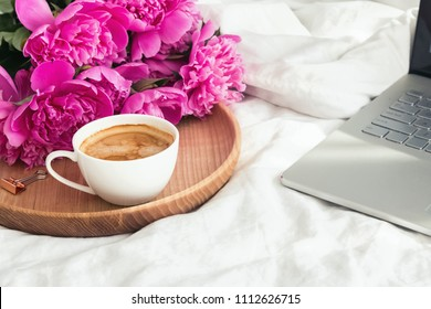Coffe, peonies and laptop on the bed. Work from home concept