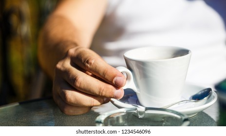 Coffe time. Hand of man hold coffee or coffe cup at cafe in the morning. Cup of coffee. Cappuccino and black espresso coffe cup. Coffee drink. Close up of a man hands holding a hot coffe cups. Closeup