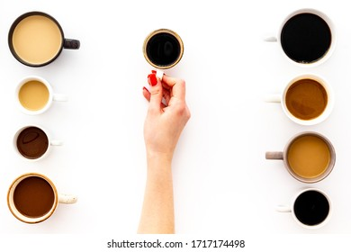 Coffee addiction. Mug in hand, many cups on white desk from above