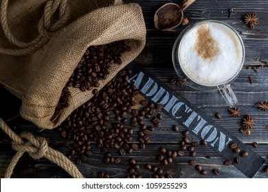 Coffee addiction with wooden background, jute bag, spices and coffee beans