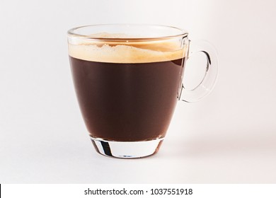Coffee americano in a transparent cup and saucer on a white background