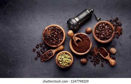 Coffee, anise, cardamon and nutmeg on black background.