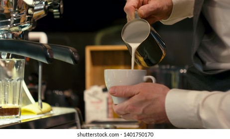 Coffee Art: Barista is Making Cappuccino Pouring Milk Foam to the White Ceramic Cup in the Cafe Shop