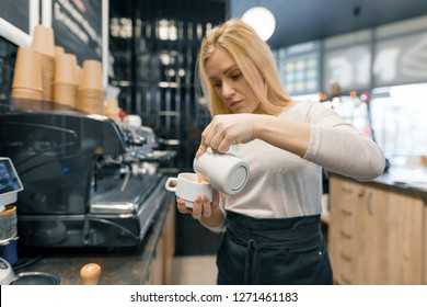 Coffee art, close-up of young beautiful female barista holding milk for prepare cup of coffee.