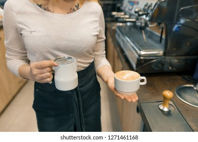 Coffee art, closeup of young female barista holding milk for prepare cup of coffee.