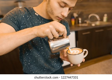 Coffee art, closeup of young male barista holding milk for prepare cup of coffee