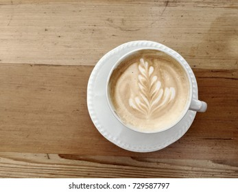 Coffee art in white cup and saucer on wooden background.
