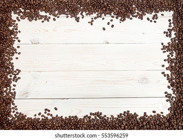 Coffee background. Heap roasted coffee beans spread over on table on four side on white background. Copy space. Top view. Place for text. View from above.
