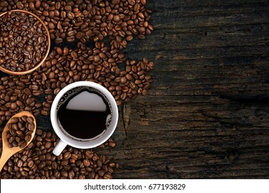 Coffee background, top view with copy space. White cup of coffee, ground coffee, coffee beans on dark wooden background