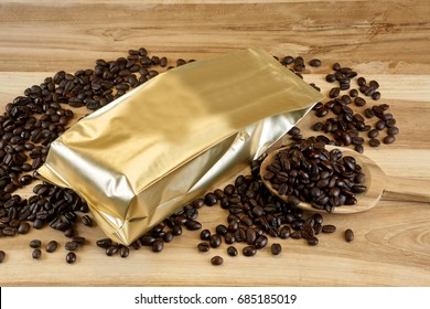 Coffee bag and packaging. The gold foil bag on the wood table with dark roasted coffee beans.