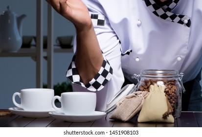 Coffee barista working late in shop preparing drinks