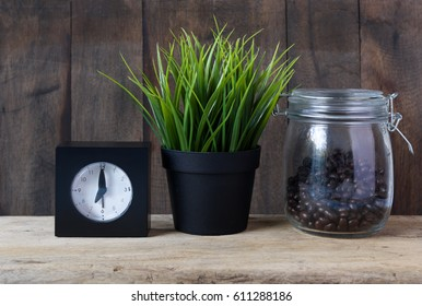 Coffee bar,roasted coffee beans,green grass pot,black alarm clock on grunge wooden table background