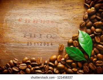 Coffee bean border on an old wood surface with stamped numbers from a shipment of coffee beans with two green leaves