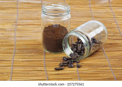 Coffee bean in glass bottle on grunge dry grass mat background