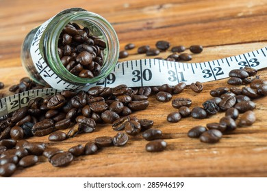 Coffee bean in glass bottle with tape measure on wooden table background