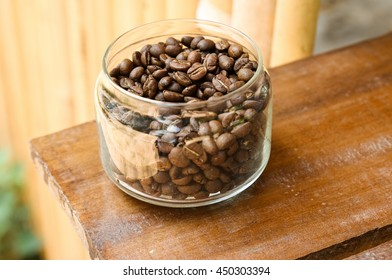 The coffee bean in a glass jar on a wooden floor.