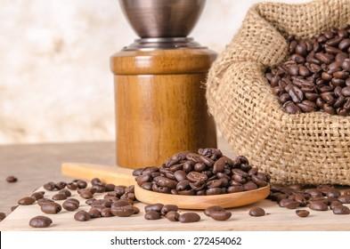 coffee bean on wood scoop ,coffee bean in bag and coffee grinder on brown wooden background