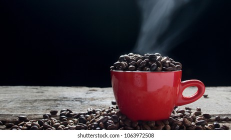 Coffee bean in the red cup with smoke. Show hot and fragrance smell from seed bean coffee.