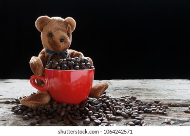 Coffee bean in the red cup with smoke and bear doll holding cup.
