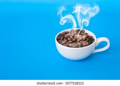 Coffee bean and with white cup hot and smoke on the blue background.