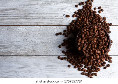 Coffee beans. Arabica grains in clay bowl on white wooden table background. Closeup, copy space, top view. Arabica seeds, roast, caffeine concept