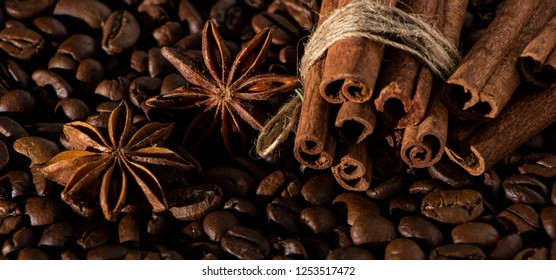Coffee beans background with different spices: anise stars and cinnamon sticks. Christmas concept.