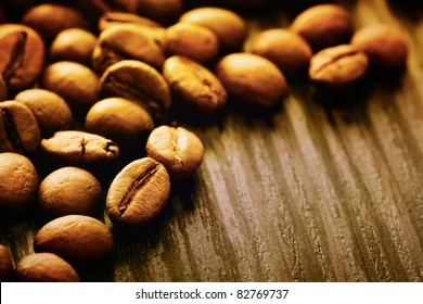 Coffee beans background macro shot on wooden background with copyspace