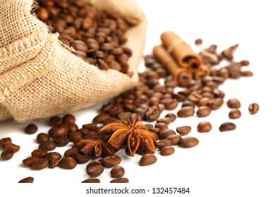 Coffee beans in bag with anise star and cinnamon sticks. Focused on foreground. Isolated on white.