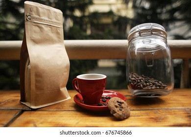 Coffee beans bag beside coffee cup and a cookie