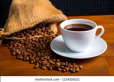Coffee beans in a bag and a cup of coffee on a wooden table