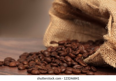 Coffee beans in coffee bag made from burlap on wooden surface with dramatic light. Focused on foreground.