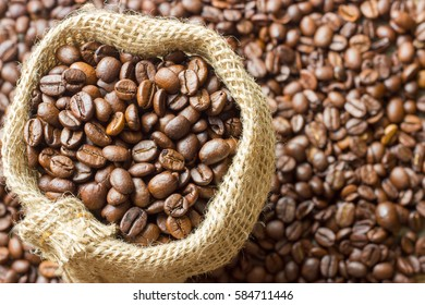 Coffee beans in coffee bag made from burlap on wooden surface. Focused in middle of the frame.