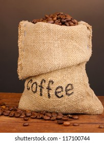 Coffee beans in bag on table on dark background