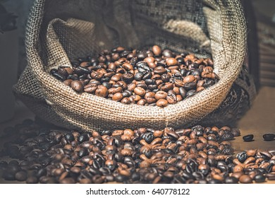 Coffee Beans in a Bag on wooden background.