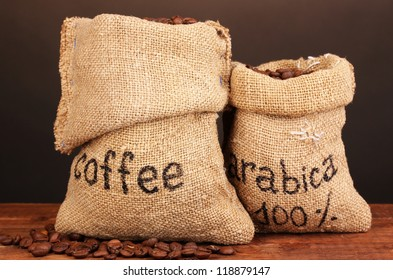 Coffee beans in bags on table on dark background