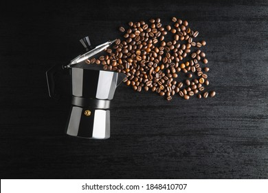 Coffee beans and bialetti coffee maker.  Moka pot on black table. Top view.