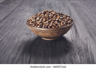 Coffee beans in brown ceramic clay bowl on blue rustic wood background. Arabica seeds heap at wooden table with copy space, soft color toning.