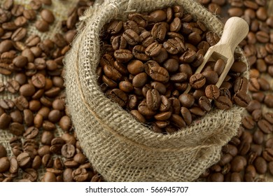 coffee beans in a burlap bag on a wooden background