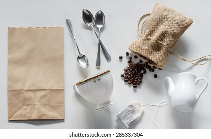 coffee beans in burlap bag, paper bag, silver spoon, vintage cup, white jar, teabag on white wood background.