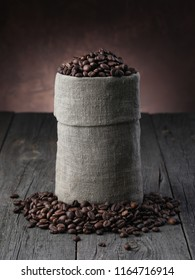 Coffee beans in burlap sack on wood background. Closeup